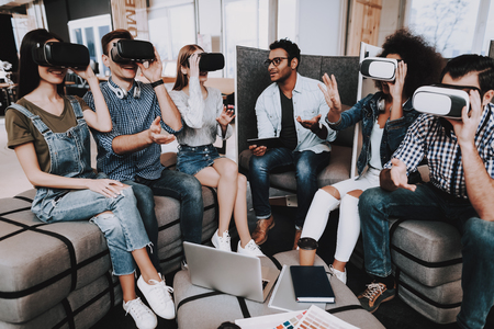 Virtual Reality Glasses. Padded Stools. Look. Designers. Young Specialists. Choose Colors for Design. Teamwork. Discussion. Brainstorming. Design Studio. Multi-Ethnic. Project. Creative. Workplace.