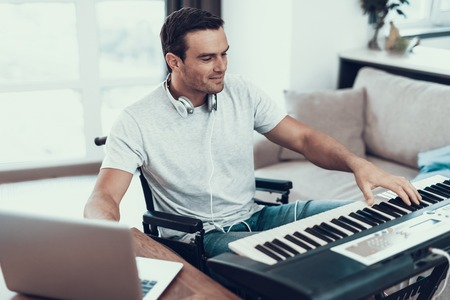 Disabled Man Composing Song with Electric Piano. Portrait of Handsome Young Handicapped Man in Wheelchair Playing Music and Writting Song with Synthesizer and Laptop While Sitting in Living Room