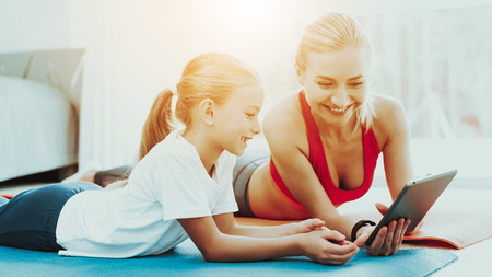 Mum And Daughter Are Staring On The Laptop Screen. Have A Break. Relaxing Together. Fitness At Home. Holiday Leisure. Body Balance. Laying On A Gym Carpet. Family Relationship.