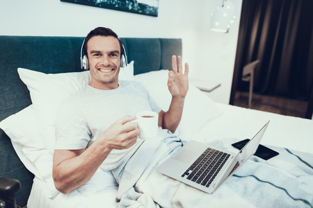 Disabled Man Uses Laptop in Bed Holds Cup of Tea. Handsome Cheerful Smiling Person Drinks Coffee in White Bed Working with Notebook on Lap Near Black Wheelchair and Shows OK Gesture