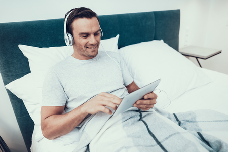 Young Man Uses Pad and Listens to Music in Bed. Handsome Cheerful Smiling Caucasian Person Relaxing in Bed With White Linens in Bright Bedroom. Man in Headphones Holds Tablet.