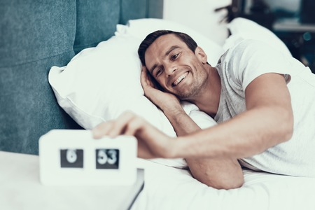 Cheerful Man Awakes and Pulls Alarm Off in Morning. Smiling Young Person in Good Mood Lying in Bedroom in Bed With White Linens Near Alarm Clock and Wearing White T-shirt. Morning Concept Imagens