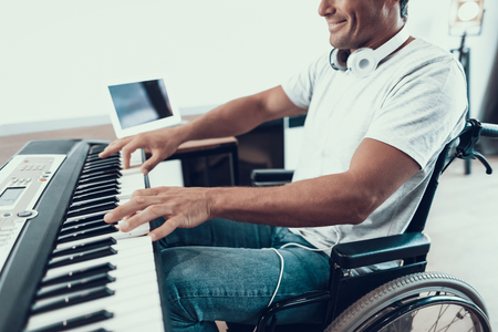 Closeup of Disabled Male Hands Plays Synthesizer. Happy Young Handicapped Man in Wheelchair Wearing White T-Shirt and Blue Jeans Playing Music on Synthesizer While Sitting in Living Room at Home
