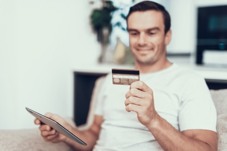 Blurred Person Holds Credit Card and Uses Tablet. Handsome Smiling Man Sitting on Couch Does Online Shopping and Showing Satisfied Face Expression in Modern Living Room at Home Banco de Imagens