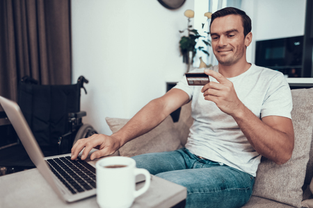 Disabled Person Holds Credit Card and Uses Laptop. Handsome Young Smiling Man Sitting on Bright Couch Near Wheelchair Does Online Shopping and Drinking Coffee in Modern Living Room