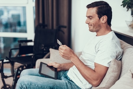 Disabled Person Holds Credit Card and Uses Tablet. Handsome Smiling Man Sitting on Couch Near Wheelchair Does Online Shopping with Satisfied Face Expression in Modern Living Room Banco de Imagens