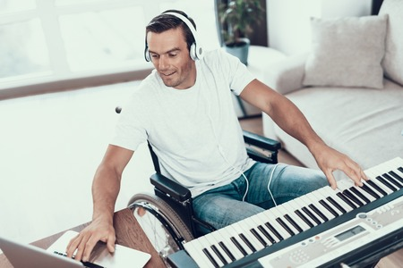 Disabled Man Composing Song with Synthesizer. Portrait of Handsome Young Handicapped Man in Wheelchair Wearing Casual Clothes Playing Music in Headphones and Using Laptop While Sitting in Living Room Stock Photo