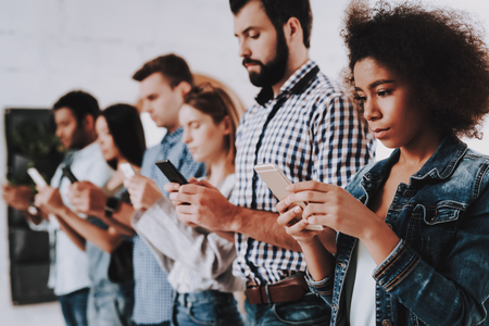 Busy. Not Pay Attention. Young People. Stand in Line. Mobile Phones. Own Affairs. Young Specialists. Look. Teamwork. Discussion. Brainstorm. Design Studio. Multi-Ethnic. Project. Creative. Workplace.