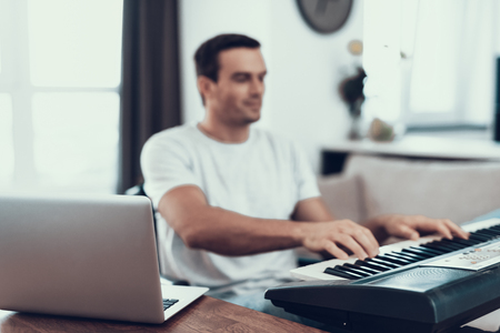 Disabled Man Composing Song with Synthesizer. Portrait of Handsome Young Handicapped Man in Wheelchair Playing Music and Composing Song with Electric Piano and Laptop While Sitting in Living Room Stok Fotoğraf