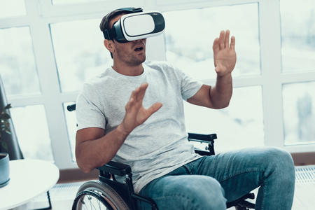 Handicapped Man in Wheelchair Wearing VR Headset. Portrait of Person in Casual Clothes Sitting Indoors and Using Virtual Reality Glasses, Keeping Hands Up and Showing Suprised Face Expression