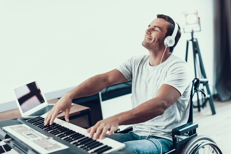 Disabled Man Playing Synthesizer in Headphones. Portrait of Handsome Young Handicapped Man in Wheelchair Playing Music on Electric Piano with Closed Eyes While Sitting in Bright Living Room at Home