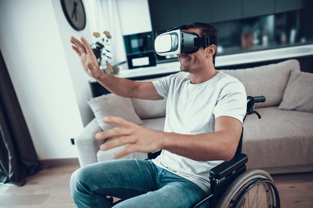Disabled Man in Wheelchair Wearing VR Headset. Portrait of Happy Person Sits in Large Bright Living Room Wears Casual Clothes Enjoys Virtual Reality Goggles and Spreads Hands to Sides