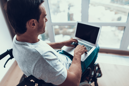 Closeup of Disabled Man Uses Laptop and Typing. Handsome Person Wears T-Shirt and Blue Jeans Sits in Wheelchair Indoors Browses Internet Holding Notebook on Lap. Disability and Work Concept Banco de Imagens