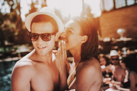 Young Smiling Couple Talking at Pool Party. Beautiful Black Woman in Bikini Whispering to Young Man wearing Hat and Sunglasses at Poolside. Happy Friends Enoying Pool Party. Summer Vacation Concept