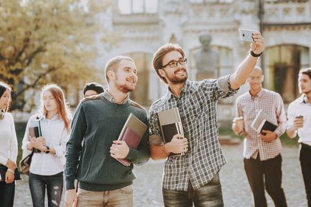 Selfi. Students. Guys. Books. Standing in University. Good Mood. Intelligence. Standing Together. Outside. Sunny Day. Students. Holding Friends. Happy. Courtyard. Books. University. Knowledge. Stock Photo