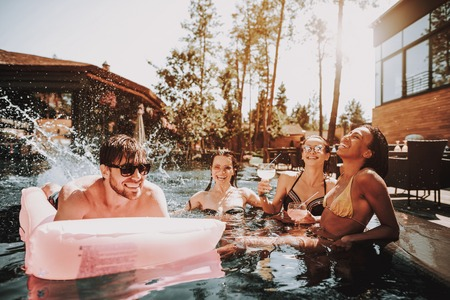 Group of Young Happy People Swimming in Pool. Young Smiling Friends wearing Sunglasses Laughing and Relaxing Together in Outdoor Hotel Pool next to Poolside. Summer Vacation Concept. Pool Party