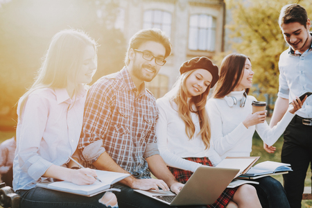 Group of Young People. Sit. Freelance. Hipster. Knowledge. Architecture. Courtyard. University. Students. Study Together. Good Mood. Laptop. Textbooks. Have Fun. Notebooks. Friendship.