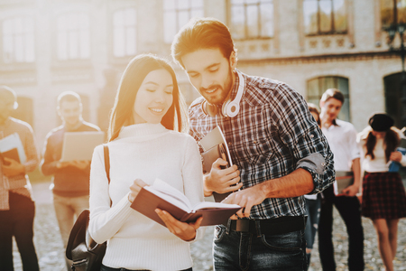 Happy. Students. Books. Intelligence. Man and Woman. Standing Together. Outside. Sunny Day. Students. Holding Friends. Courtyard. Books. Standing in University. Good Mood. University. Knowledge. Stock Photo