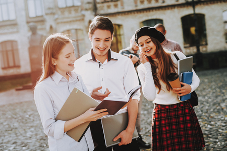 Books. University. Two Girls and Boy. Together. Courtyard. Sunny Day. Students. Holding Books. Standing in University. Good Mood. Intelligence. Standing Together. Outside. Friends. Happy. Knowledge. Stock Photo