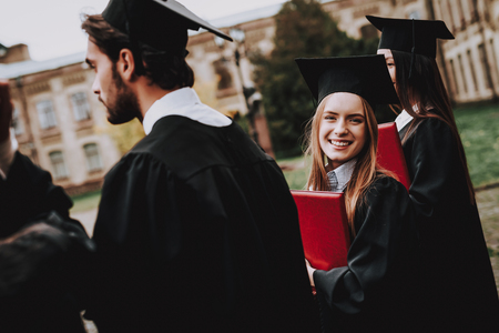 Girl. Courtyard. Mantle. University. Classmates. Cheerful. Celebration. Happiness. Intelligence. Diploma. University. Graduate. Happy. Good Mood. University. Cap. Campus. Architecture. Man. Knowledge. Stock Photo
