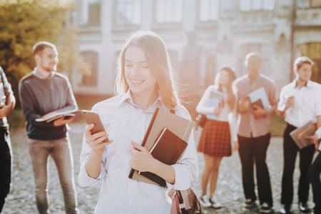 Phone. Knowledge. Intelligence. Girl. Happy. Students. Courtyard. Books. Standing in University. Good Mood. University. Architecture. Happiness. Diploma. Celebration. Campus. Man. Friends. Stock Photo