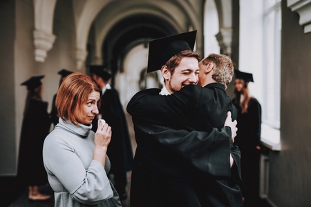 Son. Hugs. Parents. Congratulations. Student. Finish Studies. University. Graduates. Happy. Good Mood. Have Fun. Architecture. Happiness. Relations. Diploma. Standing. Corridor. Mother. Father.