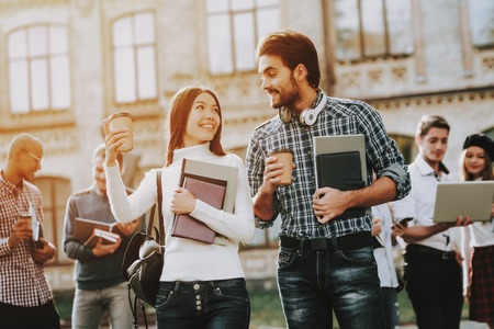 Happy. Students. Man and Woman. Students. Holding Books. Friends. Intelligence. Courtyard. Books. Standing in University. Good Mood. University. Standing Together. Outside. Sunny Day. Knowledge.