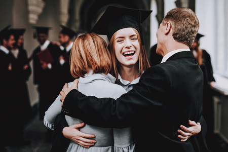 Relations. Diploma. Parents. Congratulations. Student. Finish Studies. University. Graduates. Happy. Good Mood. Have Fun. Architecture. Happiness. Standing. Corridor. Mother. Father. Daughter.