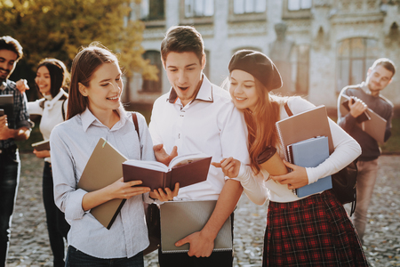 Holding Books. Two Girls and Boy. Knowledge. Standing in University. Together. Courtyard. Sunny Day. Students. Good Mood. Intelligence. Standing Together. Outside. Friends. Happy. Books. University.