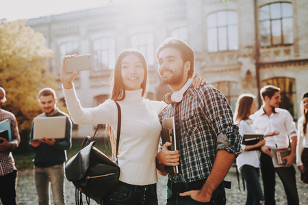 Selfie. Holding Books. Intelligence. Man and Woman. Standing Together. Outside. Sunny Day. Friends. Happy. Students. Courtyard. Books. Standing in University. Good Mood. University. Knowledge. Reklamní fotografie