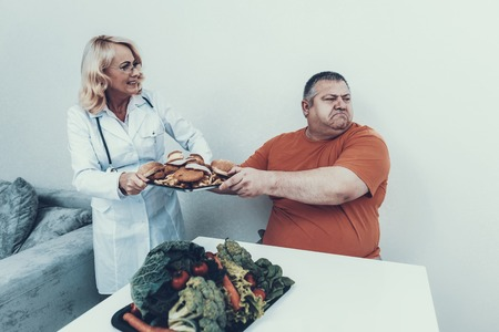 Doctor in White Coat Offers Vegetables to Fat Man. Man with Bulimia.