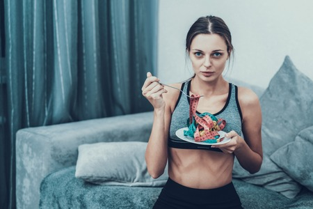 Young Woman with Tailors centimeter on Plate. Girl with Tailors Centimeter. Diet and Healthcare Concepts. Woman in White Room. Young Girl with Anorexia. Woman in Bra. Girl on Diet.
