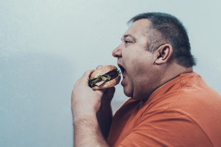 Hungry Fat Mat en camiseta naranja con hamburguesa. Hombre con Bulimia.