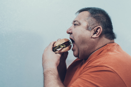 Hungry Fat Mat in Orange T-shirt with Burger. Man with Bulimia. Foto de archivo