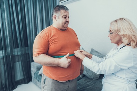 Fat Man with Doctor in White Coat in Gray Room. Woman with Tailors Centimeter. Diet and Healthcare Concept.
