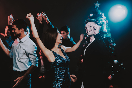 Happy Young People Dancing on New Year Party. Happy New Year. People Have Fun. Indoor Party. Celebrating of New Year. Young Woman in Dress. Young Man in Suit. Happy People. Modern Dances.