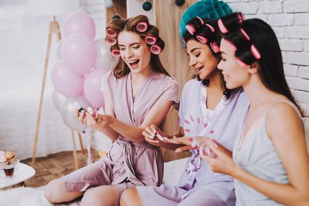 Celebrating Women's Day. Emotional Women. Watching Manicure. International Women. Happy Womens Day. Two Emotional Women. Happy Face. Nail Polish for Manicure. Curlers in Hair. White Interior. Standard-Bild - 109692430