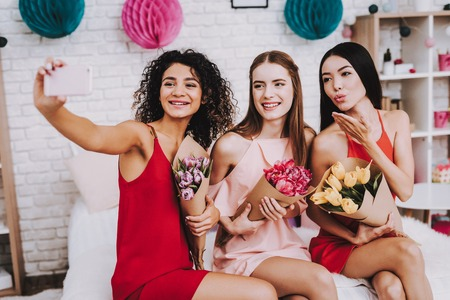 Make Selfie. Girlfriends with Flowers. Celebrating Women's Day. Emotional Women. Cheerful Women. Beautiful Girl. Womans Emotion. Bouquets in Hands. International Women with Gifts. White Interior.