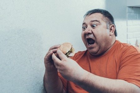 Hungry Fat Mat in Oranfe T-shirt with Burger. Man with Bulimia. Unhealthy Lifestyle Concept. Man with Overweight. Unhealthy Food. Open Mouth. Excited Man. Diet and Healthcare Concept.