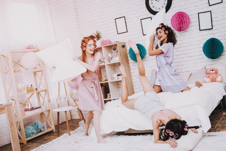 Fight Pillows. Home Party. Women in Bathrobes. White Pillows. Bright Room. White Interior. Beautiful International Woman. Girl Fell Out Bed. White Pillow in Hand. Funny People. Women with Pink Curlers