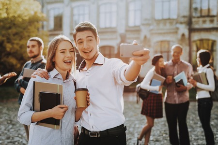 Selfi. Holding Books. Standing in University. Good Mood. Intelligence. Man and Woman. Standing Together. Outside. Sunny Day. Students. Friends. Happy. Courtyard. Books. University. Knowledge. Stock Photo