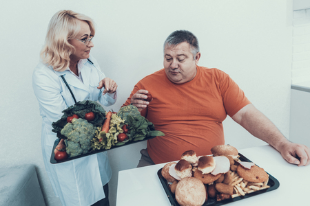 Doctor in White Coat Offers Vegetables to Fat Man. Man with Bulimia. Unhealthy Lifestyle Concept. Sitting Man. Woman in White Coat. Patient with Stomach. Man with Overweight. Vegetarian Food.