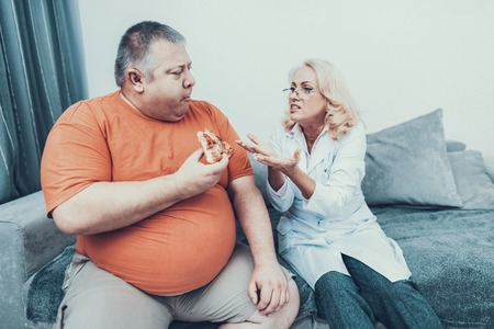 Upset Doctor in Coat near Fat Man with Pizza. Man with Bulimia. Unhealthy Lifestyle Concept. Sitting Man. Eating Pizza. Woman in White Coat. Patient with Stomach. Man with Overweight.
