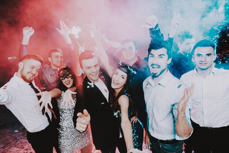 Smiling People Celebrating New Year on Party. Happy New Year. People Have Fun. Indoor Party. Celebrating of New Year. Young Woman in Dress. Young Man in Suit. Excited People. Hands Up.