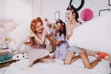 Home Party. Women in Bathrobes. White Pillows. Bright Room. White Interior. Beautiful International Woman. Smiling Girls. White Pillow in Hand. Funny People. Women with Pink Curlers. Fight Pillows.