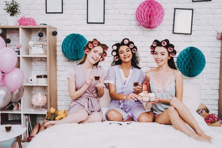 Three Women Curlers in Hair. White Interior. Girl Lying on Bed. Celebrating Womens Day. Emotional Women. Bed with White Plaid. International Women. Happy Womens Day. Smiling Women with Cupcakes.