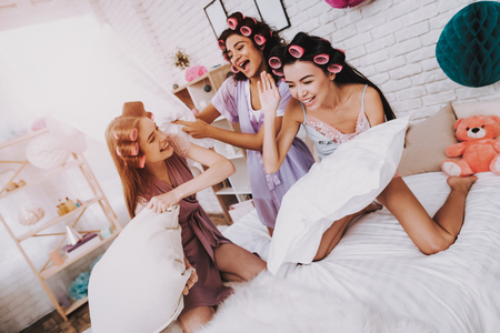 Women in Bright Room. Fight Pillows. Home Party. White Pillows. Bright Room. White Interior. Beautiful International Woman. Smiling Girls. White Pillow in Hand. Funny People. Women with Pink Curlers.