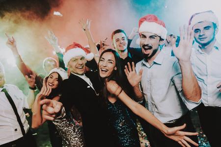 Mensen in Santa Claus Cap Nieuwjaar vieren. Gelukkig nieuwjaar. Mensen hebben plezier. Indoor feest. Nieuwjaar vieren. Jonge vrouw in jurk. Jonge man in pak. Blije mensen. Rode pet. Stockfoto - 109914217