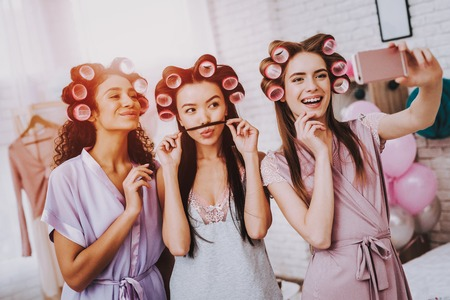Celebrating Women's Day. Emotional Women. White Interior. International Women. Happy Womens Day. Smiling Women Make Selfie. Happy Face. Smiling Girls with Phone. Women with Curlers in Hair.