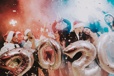 Smiling People with Baloons Celebrating New Year. Celebrating of New Year. Young Woman in Dress. Young Man in Suit. Santa Claus Cap. People with Gray Baloons. Happy New Year. People Have Fun. Banque d'images